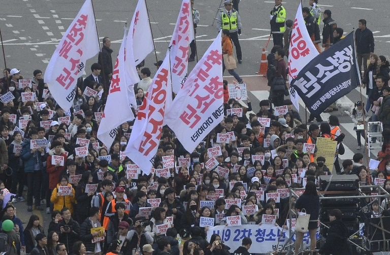 South Koreans take to the streets to demand President Park Geun-Hye to step down in Seoul on November 19, 2016. Tens of thousands of protestors gathered in Seoul for the fourth in a weekly series of mass protests aimed at forcing President Park Geun-Hye to resign over a corruption scandal. / AFP PHOTO / AFP PHOTO AND POOL / Kim Min-Hee