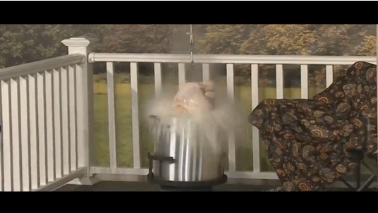 Frozen turkey being lowered in the into hot deep fryer when the oil explodes, sending fires in the different parts of the prototype house. (Photo courtesy of Reuters video file)