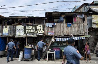 "Police officers conduct an ""Oplan Tokhang"" or house-to-house campaign on illegal drugs at an informal settlers' community in Manila on October 6, 2016.  Philippine President Rodrigo Duterte told all his critics to ""go to hell"" on October 6, as he renewed his threats to kill, after a poll showed Filipinos overwhelmingly endorsed his deadly war on crime.  / AFP PHOTO / NOEL CELIS"