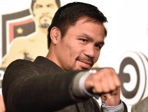"""WBO welterweight world champion Manny Pacquiao poses for the media following a press conference at his boxing gym in Tokyo on November 25, 2016. WBO welterweight world champion Manny Pacquiao on November 25 kept alive hopes for a rematch with Floyd Mayweather, saying the epic clash was """"possible"""" but only if his arch rival returns to the ring. / AFP PHOTO / KAZUHIRO NOGI"""