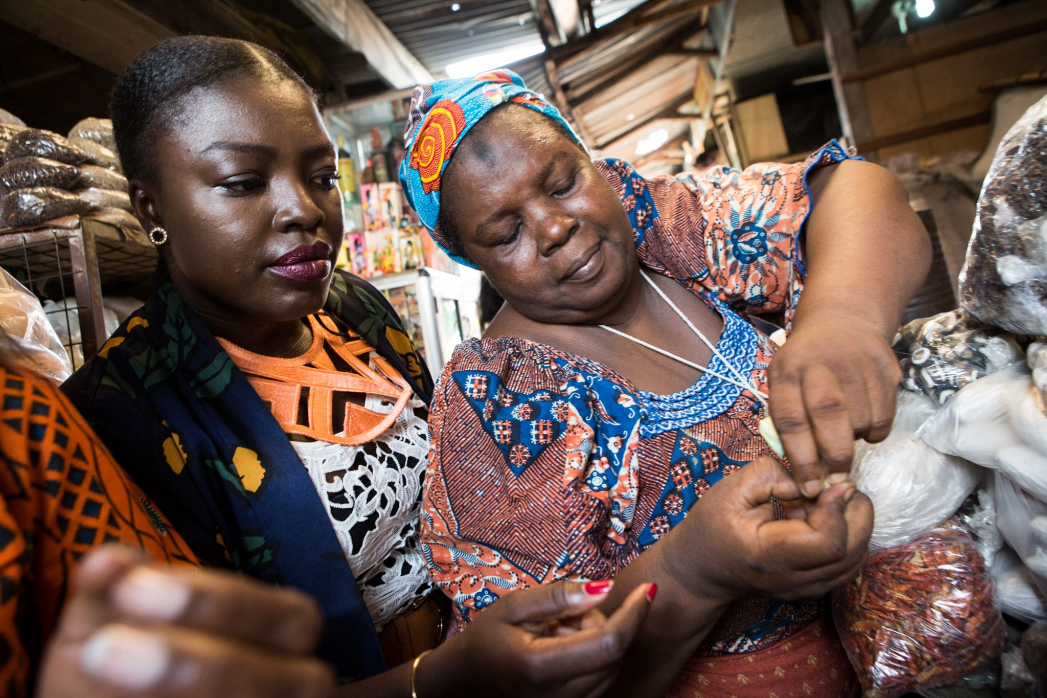 Essie Bartels buys spices from her seller Aisha Ibrahim at the Makola market in Accra, on January 25, 2017. It took a move to the United States from Ghana to convince food entrepreneur Essie Bartels that the world deserved to know more about west African cuisine. Bartels saw a gap in the market and dedicated herself to creating sauces and spice blends inspired by her childhood in Ghana's capital, Accra, through her company Essie Spice. / AFP PHOTO / Ruth McDowall