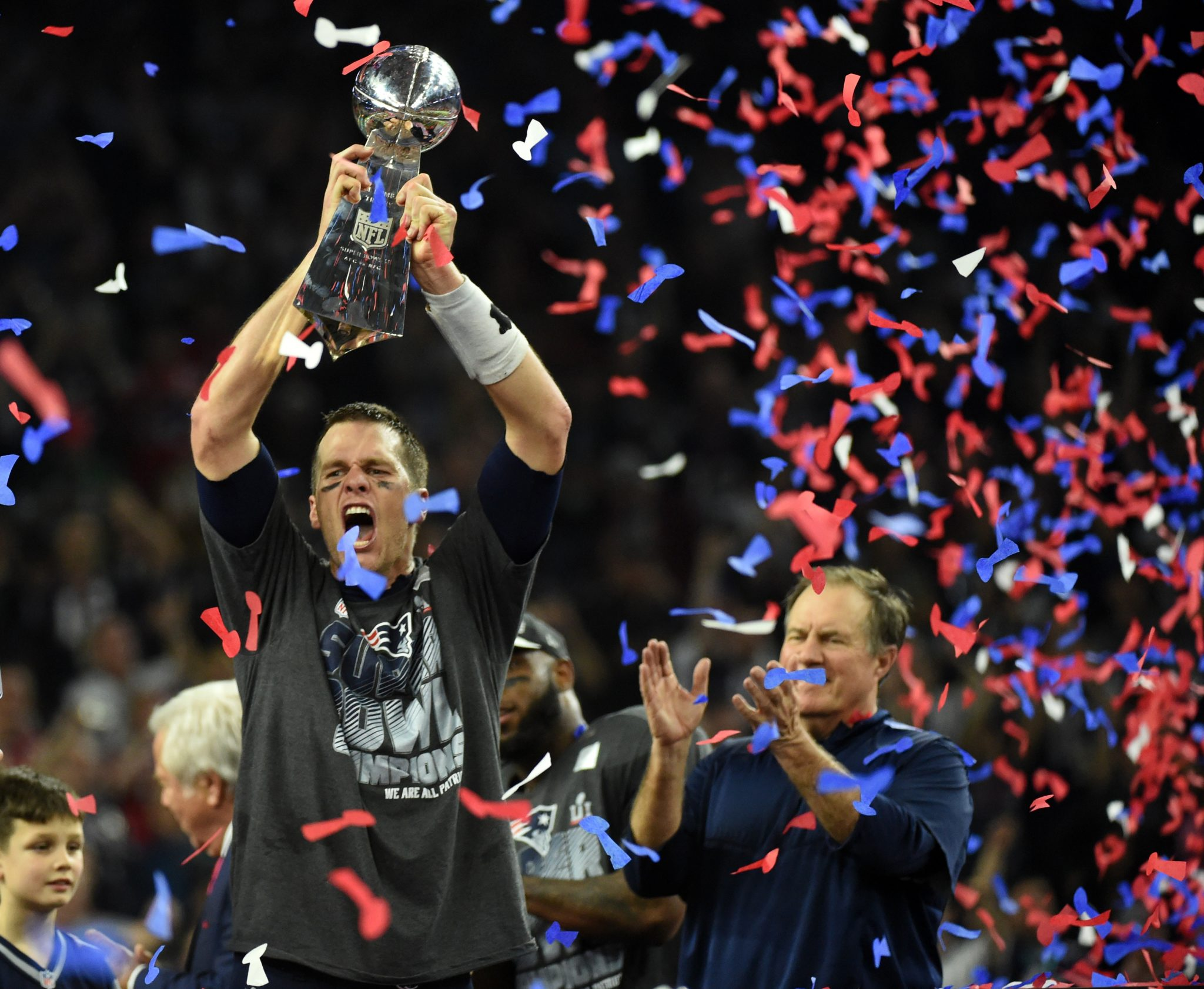 Tom Brady #12 of the New England Patriots holds the Vince Lombardi Trophy as Head coach Bill Belichick (R) looks on  after defeating the Atlanta Falcons 34-28 in overtime during Super Bowl 51 at NRG Stadium on February 5, 2017 in Houston, Texas. The Patriots defeated the Falcons 34-28 after overtime.  / AFP PHOTO / Timothy A. CLARY
