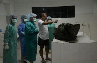 Coroners at a funeral house look at a body body containing the remains of German hostage Jurgen Kantner in Jolo, Sulu province, on the southern island of Mindanao on March 5, 2017.   The Philippine military said on Sunday it had recovered the body of an elderly German hostage who was beheaded by Islamic militants last week. The Abu Sayyaf, a kidnap-for-ransom network in the southern Philippines that has pledged allegiance to the Islamic State group, killed Jurgen Kantner, 70, after its demands for 600,000 USD were not met. / AFP PHOTO / NICKEE BUTLANGAN
