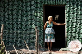 Eighty-six-year-old Maria Ponce, stands at the door of her house -- made out of plastic bottles -- in the village of El Borbollon, El Transito, west of San Salvador, on March 14, 2017. Maria built her house out of plastic bottles 12 years ago because she could not afford to build a conventional home. / AFP PHOTO / Marvin RECINOS