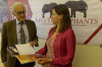 Iain  Douglas -Hamilton, founder of Save The Elephants (STE) and leading authority on the African Elephant (L) accompanied by Lucy Vigne, Ivory researcher, look at a report documenting the decline of the wholesale price of raw ivory in China, on March 29, 2017 in Nairobi.  / AFP PHOTO / SIMON MAINA