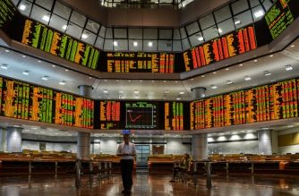 A man (R) eats a banana as he monitors stock movements at a private trading firm in Kuala Lumpur on January  7, 2016. Chinese markets were suspended on January 7, for the second day this week after they fell more than seven percent, leading an Asia-wide sell-off as Beijing weakened the value of the yuan currency by the most since August.  AFP PHOTO / MOHD RASFAN / AFP PHOTO / MOHD RASFAN