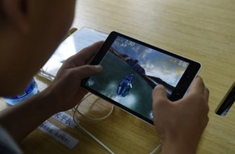 A customer plays a game on a Xiaomi Mi Pad tablet at a Xiaomi service center in Beijing on August 5, 2015.  Chinese company Xiaomi was the largest smartphone vendor in China based on shipments with a 15.9 percent market share in the second quarter of 2015, according to Canalys. Telecom equipment maker Huawei was close behind at 15.7 percent, it said, followed by Apple, South Korea's Samsung and Chinese firm Vivo. AFP PHOTO / GREG BAKER / AFP PHOTO / GREG BAKER