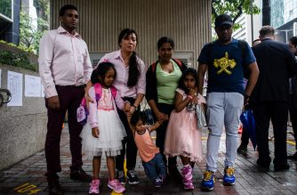 Sri Lankan refugee Ajith Puspa (back L), Filipino refugee Vanessa Rodel (back 2nd L), her daughter Keana (front L), Sri Lankan refugee Nadeeka (back 3rd L), her partner Supun Thilina Kellapatha and their children, son Danath (front C) and daughter Sethumdi (front R) pose for the press outside the Immigration Tower in Hong Kong on May 15, 2017.  A group of refugees who sheltered fugitive whistleblower Edward Snowden in Hong Kong are facing deportation after the city's authorities rejected their bid for protection, their lawyer said on May 15. / AFP PHOTO / ANTHONY WALLACE