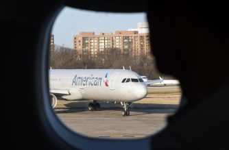 "(FILES) This file photo taken on February 24, 2017 shows a passenger looking out his window at an American Airlines plane at Reagan National Airport in Arlington, Virginia. American Airlines said on July 12, 2017,  it is ending its codeshare relationships with Qatar Airways and Etihad Airways as part of its push against government subsidies of Middle Eastern carriers. American notified Doha-based Qatar Airways and Abu Dhabi-based Etihad of its decision on June 29 to end the ""codeshare"" partnership -- the sharing of a flight by two carriers.  / AFP PHOTO / ANDREW CABALLERO-REYNOLDS"