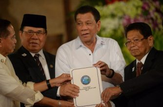 """(L to R) Philippine Secretary of the Peace Process Jesus Dureza, Al-Hajj Murad, chairman of the Moro Islamic Liberation Front (MILF), Philippine President Rodrigo Duterte and Ghazali Jaafar, vice chairman of MILF, join hands holding a proposed draft of the Bangsamoro Basic Law (BBL) during a ceremony at the Malacanang Palace in Manila on July 17, 2017. Duterte offered """"genuine autonomy"""" to the Philippines' Muslim minority on July 17 to help him defeat Islamist militants who seized a southern city in the gravest challenge to his year-old rule. / AFP PHOTO / TED ALJIBE"""