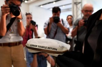 (FILES) This file photo taken on July 13, 2017 shows Sotheby's Cassandra Hatton as she displays the Apollo 11 Contingency Lunar Sample Return Bag, used by Neil Armstrong on Apollo 11 to bring back the very first pieces of the moon ever collected, during a media preview for Space Exploration auction in New York.  A bag Neil Armstrong used to collect the first ever samples of the moon -- which was once nearly thrown out with the trash -- sold at auction on July 20, 2017 for $1.8 million, Sotheby's said.The outer decontamination bag, which was flown to the moon on Apollo 11 and still carries traces of moon dust and small rock, was sold on the 48th anniversary of the first moon landing in 1969. / AFP PHOTO / Jewel SAMAD