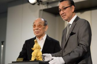 Japanese actors Akira Takarada (R) and Haruo Nakajima (L) pose beside the 24-cm-tall and 15-kilogram gold statue of Godzilla unveiled during a press preview of the Godzilla exhibition in Tokyo on July 19, 2014. The Godzilla statue will take orders starting on July 20 at the Ginza Tanaka jewelry shop with a price of 150 million yen (about 1.48 million USD). AFP PHOTO/Toshifumi KITAMURA