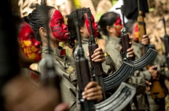 This photo taken on July 30, 2017 shows guerrillas of the New People's Army (NPA) in formation in the Sierra Madre mountain range, located east of Manila. Fuelled by one of the world's starkest rich-poor divides, a Maoist rebellion that began months before the first human landed on the moon plods on even though the country now boasts one of the world's fastest-growing economies. / AFP PHOTO / Noel CELIS / TO GO WITH Philippines-unrest-communist-peace,FOCUS  by Cecil MORELLA