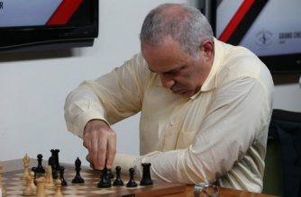Grandmaster chess player Garry Kasparov makes a move in a match against grandmaster Levon Aronian during day two of the Grand Chess Tour at the Chess Club and Scholastic Center in St. Louis on August 15, 2017.  Kasparov and other chess grandmaters are in St. Louis to compete in the Grand Chess Tour. Kasparov was World Champion for decades.  / AFP PHOTO / BILL GREENBLATT
