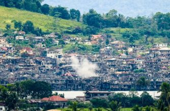 "Smoke billows from destroyed buildings after government troops fired mortars at an Islamic State position in Marawi on the southern island of Mindanao on October 15, 2017.  Philippine troops on October 15 bombed militants loyal to the Islamic State group who have held out for over four months in a southern city and the military said the conflict would be over ""very soon"". / AFP PHOTO / Ferdinandh CABRERA"