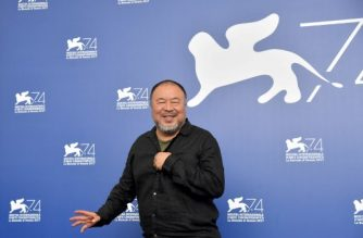 """(FILES) This file photo taken on September 1, 2017 shows Chinese artist and producer Ai Weiwei attending the photocall of the movie """"Human Flow"""" presented in competition at the 74th Venice Film Festival at Venice Lido.  In the most tender moments of """"Human Flow,"""" Ai Weiwei's epic documentary on the worldwide migrant crisis, he is seen hugging, cooking with and cutting the hair of refugees. An ordinary filmmaker might be accused of getting too close to his subject but, as far as the Chinese dissident and internationally renowned artist is concerned, he is the subject.  / AFP PHOTO / Tiziana FABI"""