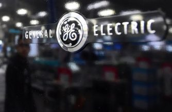 (FILES) This file photo taken on January 15, 2016 shows a man reflected on the black door of a General Electric (GE) refrigerator at a store selling electronics and appliances in Montebello, California.  Large contracts for Boeing and General Electric in Iran, while not under direct threat, face significant new uncertainties following President Donald Trump's announcement on October 13, 2017, said two people familiar with the matter. Trump stopped short Friday of killing the landmark 2015 agreement -- which curbed Iran's nuclear program in return for sanctions relief -- but he withdrew official support for the agreement and threw its prospects into grave doubt.  / AFP PHOTO / FREDERIC J. BROWN