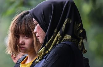(FILES) This file photo taken on March 1, 2017 shows Vietnamese national Doan Thi Huong (L), 28, being escorted with a heavy police presence after a court appearance with Indonesian national Siti Aisyah, 25, at the magistrates' court in Sepang, for their alleged role in the assassination of Kim Jong-Nam, the half-brother of North Korean leader Kim Jong-Un. Two women go on trial next week charged with murdering the half-brother of North Korea's leader, with proceedings set to shed light on the Cold War-style assassination in Malaysia that sparked a diplomatic crisis. / AFP PHOTO / MOHD RASFAN / To go with story Vietnam-corruption-politics-government, Focus by Jenny Vaughan