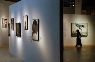 """A picture taken on September 27, 2017 shows a woman walking past Marc Chagall's """"Over the town"""" during the media preview of the exhibition titled """"A certain 1917"""" at the Tretyakov Gallery. From elegant portraits of aristocrats to scenes of protesters waving red flags, a major new exhibition of Russian art from 1917 that opened in Moscow on September 28, 2017 evokes the social turmoil of the revolutionary year. / AFP PHOTO / Maxim ZMEYEV / RESTRICTED TO EDITORIAL USE - MANDATORY MENTION OF THE ARTIST UPON PUBLICATION - TO ILLUSTRATE THE EVENT AS SPECIFIED IN THE CAPTION"""