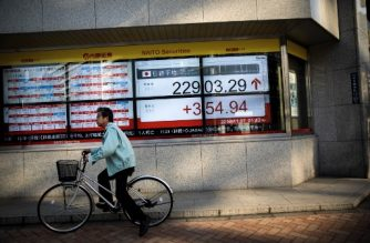 A man rides his bicycle past an electronics stocks indicator displaying share prices of the Tokyo Stock Exchange in Tokyo on November 7, 2017.  Tokyo's benchmark stock index closed a quarter century high on November 7, closing 1.73 percent higher amid eased concerns over geopolitical risks and on expectations for sound corporate performances. / AFP PHOTO / Behrouz MEHRI