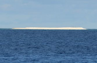 FILE PHOTO: This photo taken on April 21, 2017 shows a sandbar as seen from Philippine-held Thitu island in the Spratlys archipelago.  Philippine President Rodrigo Duterte ordered troops to scrap plans of building a fishermen's shelter on a sandbar in the disputed South China Sea after Beijing complained, his defence chief said on November 8, 2017. / AFP PHOTO / Ted ALJIBE