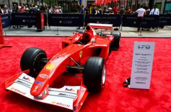 People look at former Ferrari German F1 driver Michael Schumacher's Monaco Grand Prix winning Ferrari F2001 car, which is on display with other models at the Rockefeller Plaza in New York on October 7, 2017, in celebrationS of Ferrari's 70th anniversary.  Schumacher's Monaco Grand Prix winning Ferrari F2001 will be offered at Sotheby's Contemporary Art Evening Auction on 16 November in New York, the first collector car ever to be offered in a Sotheby's art sale. / AFP PHOTO / Jewel SAMAD