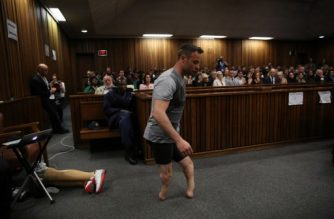 Paralympic gold medalist Oscar Pistorius prepares to walk across the courtroom without his prosthetic legs during the third day of his hearing at the Pretoria High Court for sentencing procedures in his murder trial in Pretoria on June 15, 2016. A sobbing Oscar Pistorius walked hesitantly on his stumps around court on June 15 in a dramatic demonstration of his disability ahead of his sentencing for murdering his girlfriend Reeva Steenkamp. / AFP PHOTO / POOL AND AFP PHOTO / SIPHIWE SIBEKO