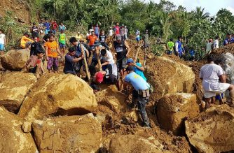 This handout photo released on December 17, 2017 by Philippine National Police Regional Office VIII (PNP-8) via their Facebook account shows police and civilian volunteers working through boulders as they look for survivors after a landslide hit a village, due to heavy rains triggered by Typhoon Kai-Tak in Naval town, Biliran province, central Philippines.  Landslides triggered by Tropical Storm Kai-Tak have killed 26 people and 23 more are missing in the eastern Philippines, authorities said on December 17. / AFP PHOTO / PNP-8 / STR