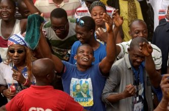 Supporters of the winner of Liberia's presidential elections George Weah celebrates after the proclamation of the second round results on December 29, 2017, outside of the Weah's headquarters in Monrovia.  Former star footballer George Weah was named winner of Liberia's presidential election on December 28, easily beating his challenger in the country's first democratic transfer of power in seven decades scarred by civil wars, political assassinations and an Ebola crisis. He will be sworn in on January 22. / AFP PHOTO / SEYLLOU