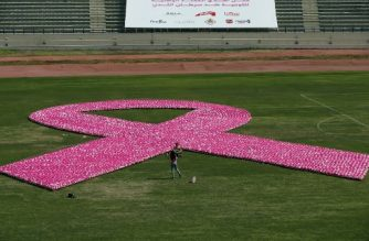 People gather around a pink ribbon, made up of eight thousand pink footballs, during an event to raise awarness on breast cancer at the Sport City Stadium in Beirut on October 8, 2017. The organizers also received a certificate from the World Record Academy for the Largest Awareness Ribbon made from Footballs. / AFP PHOTO / ANWAR AMRO