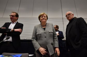 German Chancellor and head of the Christian Democratic Union (CDU) Angela Merkel (C) arrives next to CDU parliamentary group leader of the conservative CDU/CSU faction Volker Kauder (R) and parliamentary group leader of the conservative Christian Social Union (CSU) Alexander Dobrindt for a meeting in Berlin on January 29, 2018.  / AFP PHOTO / Tobias SCHWARZ