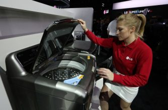 An exhibitor demonstrates an  Inverter Direct Drive washing machine at the LG exhibit at the CES 2016 Consumer Electronics Show in Las Vegas, Nevada on January 6, 2016. AFP PHOTO / DAVID MCNEW / AFP PHOTO / DAVID MCNEW