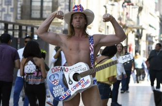 Robert John Burck, an American street performer known as the Naked Cowboy, is seen during a visit to Madero street in Mexico City on January 10, 2018.  The Naked Cowboy is in Mexico with his Mexican wife to attend a family party. / AFP PHOTO / ALFREDO ESTRELLA