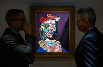 "James Mackie (L), Sotheby's senior director and head of the Department Impressionist and Modern Art, speaks with a colleague in front of Pablo Picasso's 1937 oil painting ""Femme au béret et à la robe quadrillée (Marie-Thérèse Walter)"" during a media preview at the Sotheby's showroom in Hong Kong on January 30, 2018. / AFP PHOTO / Anthony Wallace"