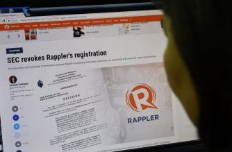 This photo illustration shows a woman reading the website of online newsportal Rappler in Manila on January 15, 2018. The Philippine government has revoked the operating license of leading news website Rappler, officials said, in a ruling denounced by President Rodrigo Duterte's critics as another blow to press freedom. / AFP PHOTO / TED ALJIBE
