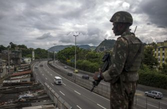 """(FILES) In this file photo taken on February 07, 2018 a Brazilian Army soldier stands guard over the """"Linha Amarela"""" (yellow line) road during a joint operation at """"Cidade de Deus"""" (City of God) favela in Rio de Janeiro, Brazil. According to matching sources on February 16, 2018 Brazilian President Michel Temer will decreet an Armed Forces' intervention in the Brazilian state of Rio de Janeiro to take the lead in the fight against organised crime.  / AFP PHOTO / MAURO PIMENTEL"""
