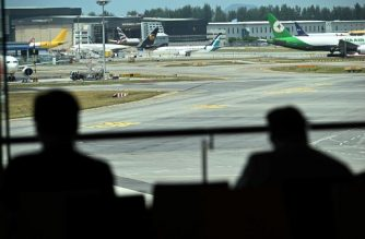 Two persons look from the viewing gallery of Changi International Airport different aircrafts including a SilkAir Boeing 737 MAX aircraft (background C) parked on the airport tarmac in Singapore on March 12, 2019. - Singapore's aviation regulator on March 12, banned the use of Boeing 737 MAX aircraft in the country's airspace following a deadly Ethiopia plane crash at the weekend. (Photo by Roslan RAHMAN / AFP)